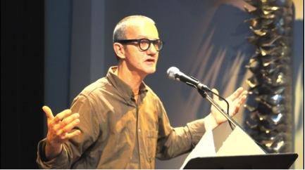 Serge Lavoie, recevant son prix, photographié devant une œuvre de Dominique Blain.