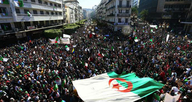 Algerians mach with a giant national flag during a protest in Algiers, Algeria, Friday, March 15, 2019. Tens of thousands of people gathered Friday in Algeria's capital and other cities amid heavy security for what could be decisive protests against longtime leader Abdelaziz Bouteflika. (AP Photo/Toufik Doudou)